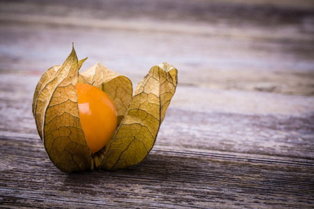 Physalis, or Cape Gooseberry fruit over old wood background. Vintage effect with intentional vignette photo