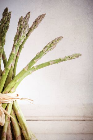 A bundle of fresh asparagus spear, tied with rafia, against vintage peeling paint effect background with space for yout text photo