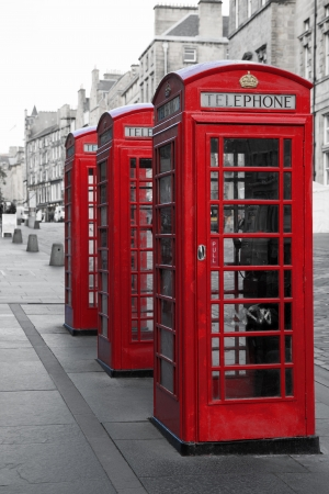 A row of classic British phone boxes on The Royal Mile, Edinburgh, Scotland  Retro effect in black and white with red photo
