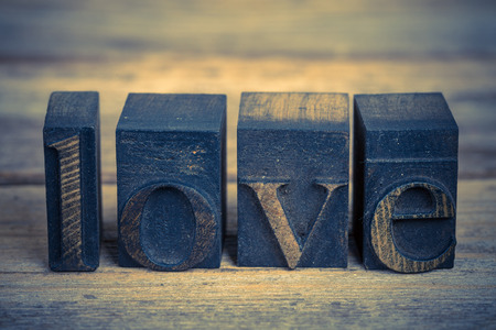 The word LOVE written with vintage printing blocks over old wood background photo