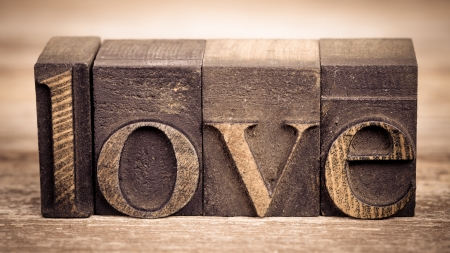 The word LOVE written with vintage printing blocks over old wood background Stock Photo - 23173873