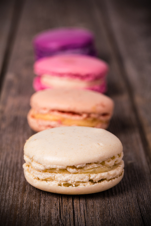 vignetting: Assorted macaroons over old wood background. Vintage effect processing with intentional vignetting