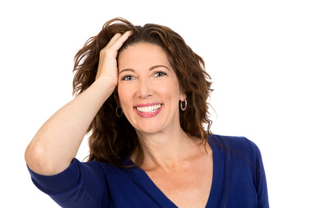 Glamorous middle aged woman smiles to the camera, whilst pushing her hair back from her face