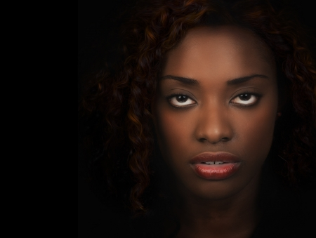 Closeup portrait of beautiful African American woman over black background  photo