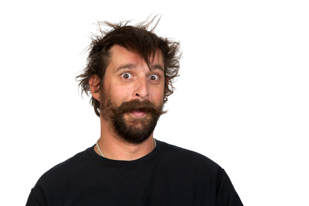 pull over: Goofy young man, with full beard and moustache and wild hair, pull a comical face to the camera  Studio portrait over white  Space for your text