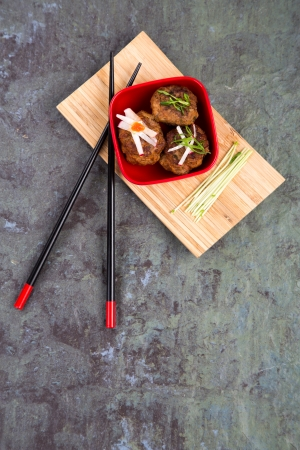 Asian meatballs, garhished with pea shoots and radish julienne, in a red bowl on bamboo tray with chopsticks, against natural slate background  Space for your text photo