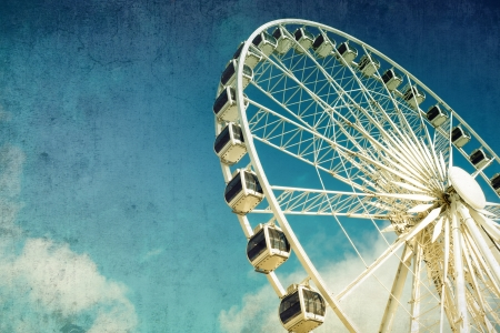Retro style image of a ferris wheel against blue sky  Cross-processed, grunge effect  photo
