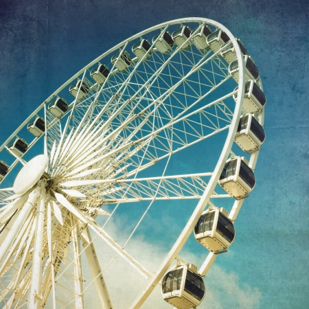 blue toned: Retro style image of a ferris wheel against blue sky  Cross-processed, grunge effect