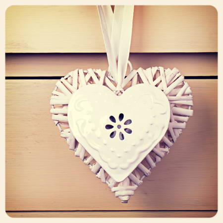 Wicker and tin heart hanging from a white ribbon  Retro style processing with intentional vignette, framed to create old-fashioned film style  Stock Photo - 23641110
