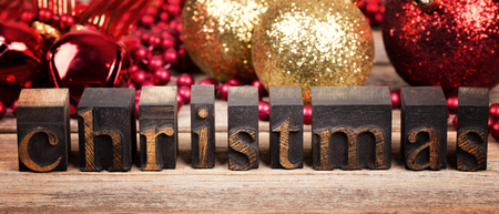The word CHRISTMAS written with vintage wood printer blocks. Christmas message over old wood with traditional tree decorations behind. photo