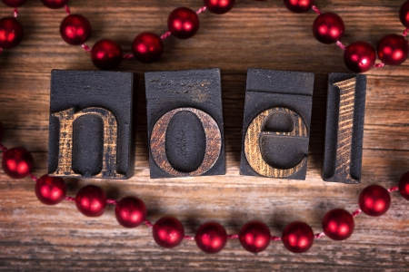 Le mot NOEL écrit avec des blocs d'impression de bois vintage. Message de Noël sur le vieux bois avec un collier de perles rouges décoratifs. Banque d'images - 23642911