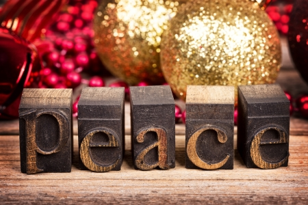 world peace: The word PEACE written with vintage wood printer blocks. Christmas message over old wood with traditional tree decorations behind. Stock Photo