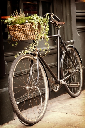 Old bike with flowers in the shopping basket, leaning against the outside of a building. Retro style processing processing with intentional vignette.