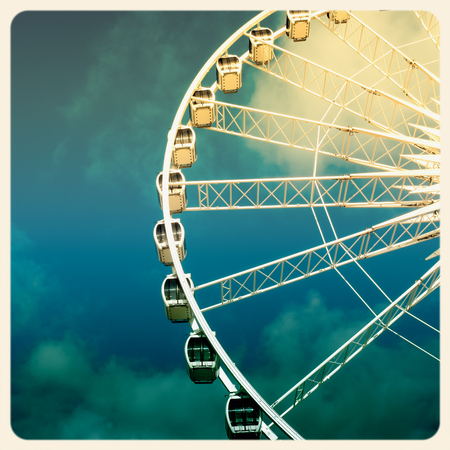 Retro style image of a ferris wheel against blue sky. Cross-processed, old instant photo effect. photo