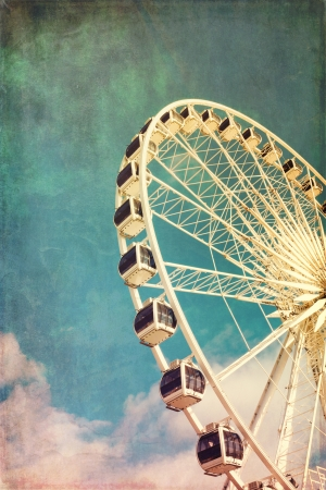 Retro style image of a ferris wheel against blue sky. Cross-processed, grunge effect. 写真素材