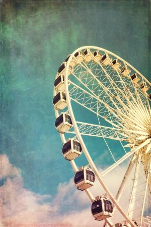 Retro stijl beeld van een reuzenrad tegen de blauwe hemel. Cross-verwerkt, grunge effect. Stockfoto
