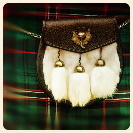 Traditional Scottish sporran over tartan background. Retro style photo. photo