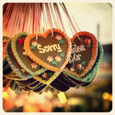 sorry: Retro effect image of Gingerbread hearts hanging in a German Christmas market. The prominent heart is iced with the word Sorry. Cross-processed and textured to emulate an old instant photo. Stock Photo