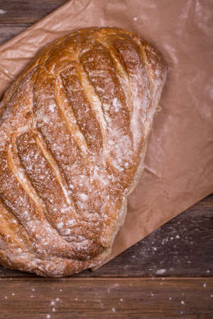 bloomer: Crusty bloomer loaf, unwrapped from brown paper wrapping, over old wood background