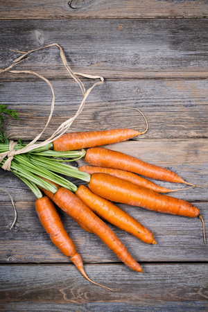 Bunch of carrots over old wood background photo