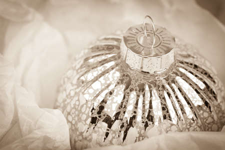 tarnish: Antique style glass Christmas tree ornament, wrapped in tissue paper. Vintage style processing with intentional vignette Stock Photo