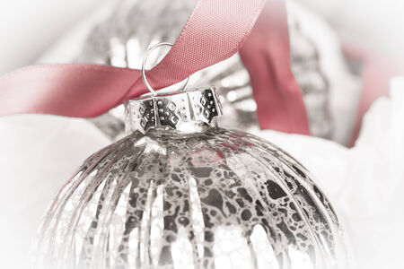 tarnish: Antique glass Christmas tree baubles wrapped in procective tissue, and threaded on to a red satin ribbon.