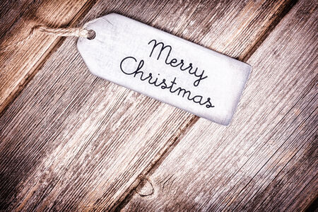 Metal tag with string, wishing a Merry Christmas, over old wood surface. Retro style processing. Stock Photo - 24494304