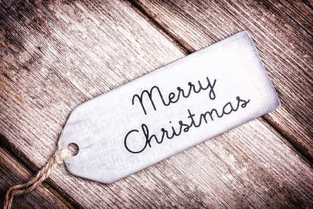 Metal tag with string, wishing a Merry Christmas, over old wood surface. Retro style processing. Stock Photo - 24494305