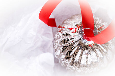 antique glass Christmas tree baubles wrapped in protective tissue, and threaded on to a red satin ribbon. Space for your text photo