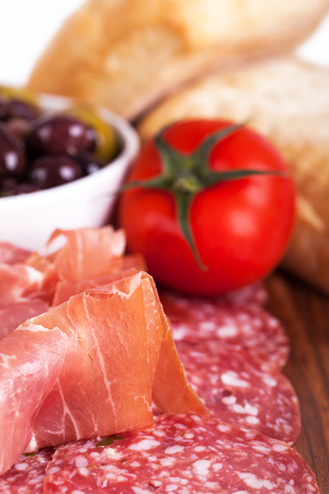 A platter of cold meats, olives, tomato and bread rolls  Tapas style assortment  Intentional shallow depth of field  photo