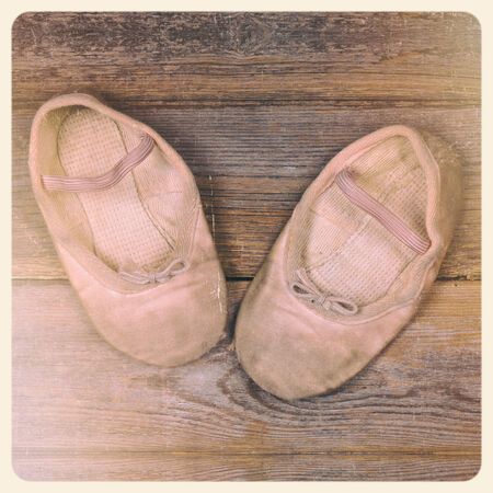 A pair of tiny ballet shoes on old wood floor, with nostalgic feel suitable for mother photo