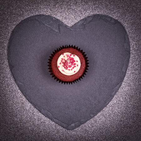 Valentine day gift of a red velvet cupcake over a slate heart  photo