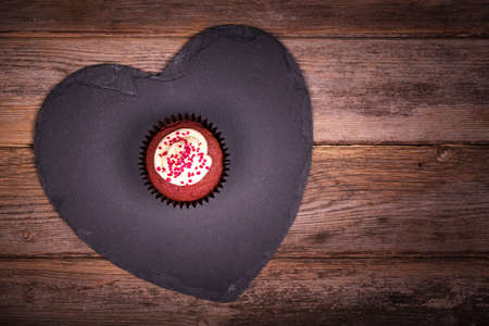 Valentine day gift of a red velvet cupcake on a slate heart, over old wood background  photo