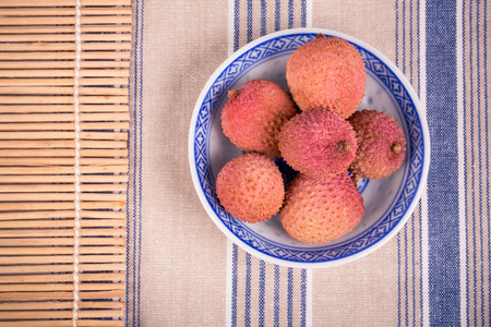 lychee: Lychees in a traditional Chinese blue and white bowl with bamboo mat and striped tablecloth Stock Photo