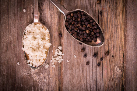 tarnish: Vintage effect image of tarnished silver spoons filled with salt crystals and black peppercorns
