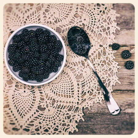 A bowl of fresh blackberries with spoon, over antique lace tablecloth and old wood background  Filtered to look like an aged instant photo  photo