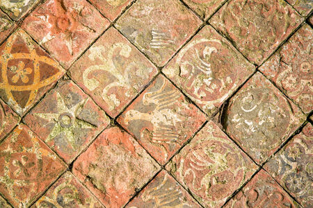 Ancient decorative quarry tile floor, depicting birds, flowers and stars  photo