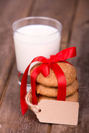 Glass of milk and a stack of homemade cookies, tied with a red ribbon and a gift tag, with space for your text, over old wooden background  photo