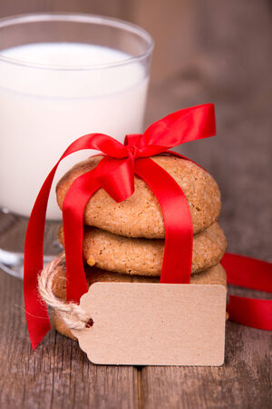 homemade style: Glass of milk and a stack of homemade cookies, tied with a red ribbon and a gift tag, with space for your text, over old wooden background