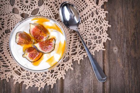 greek pot: Yogurt greco con fichi e miele, in una ciotola di vetro sopra la vecchia tovaglia di pizzo.