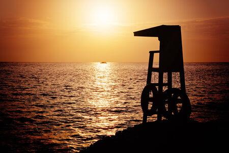 sheik: Lifeguard tower silhouette against sunrise over the Red Sea, Sharm el Sheik, Egypt  Stock Photo
