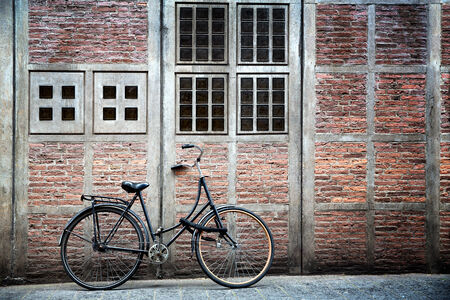 parked bicycles: Old bike leaning against a decorative wall, Amsterdam
