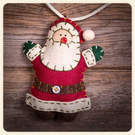 Handicraft Christmas decoration, felt Santa Claus, over old wood background.  Filtered to look like an aged instant photo. photo
