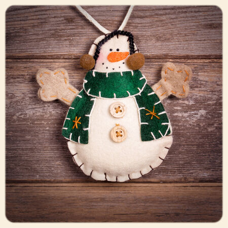 Handicraft Christmas decoration, felt snowman, over old wood background.  Filtered to look like an aged instant photo.  photo