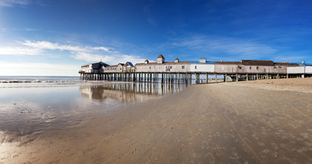 old pier: Early morning at Old Orchard beach, Maine, USA. Panorama showing the old wooden pier, sea and sand before the arrival of the daily crowds.