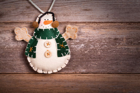 Hand made felt snowman Christmas decoration. Vintage style, over old wood background, with space for your text.