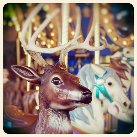 christmas reindeer: A Christmas reindeer on a carousel ride. Processed  and filtered to look like an aged instant photo.