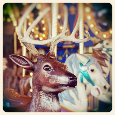 renos de navidad: Un reno de la Navidad en un paseo en carrusel. Procesado y se filtró para parecer una foto instantánea de edad.