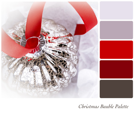 An antique glass Christmas tree decoration, on a red ribbon, and nestled in tissue paper wrapping. In a colour palette with complimentary colour swatches. photo