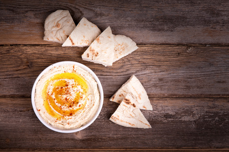 A bowl of fresh hummas, drizzled with olive oil and paprika, served with wedges of pita bread.